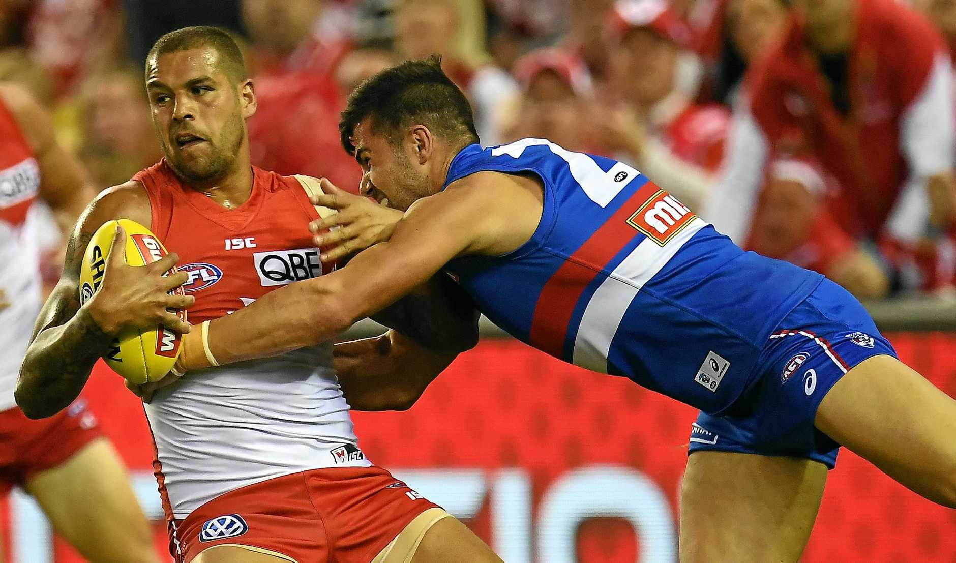 Lance Franklin of the Swans (left) is tackled by Marcus Adams of the Western Bulldogs.