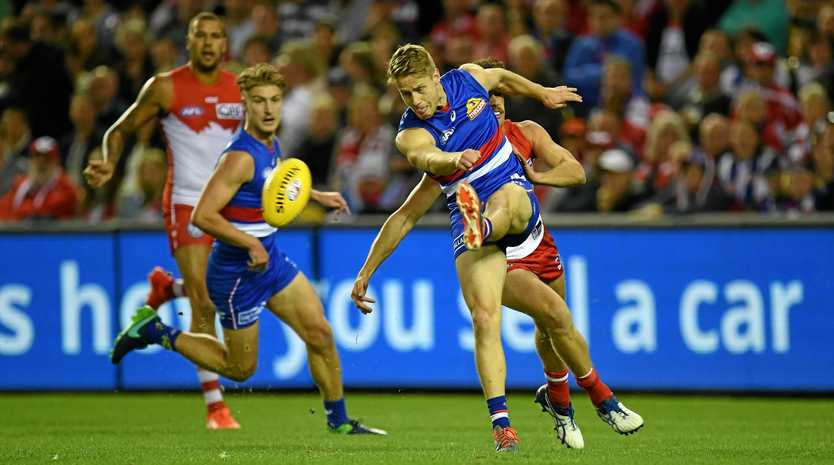 Lachie Hunter of the Bulldogs boots the ball downfield.