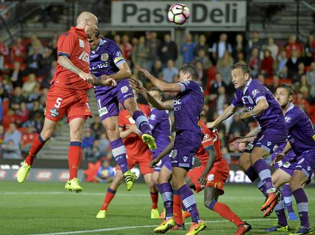 Taylor Regan of Adelaide United heads the ball towards goal.