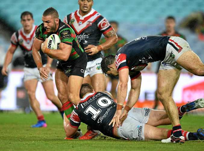 Robbie Farah of the Rabbitohs is tackled by Dylan Napa and Aidan Guerra of the Roosters.