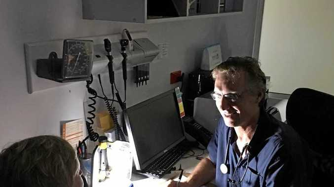 Dr John McIntosh of the GP Superclinic has been busy seeing patients by torchlight as his clinics have been without power in the wake of Cyclone Debbie.