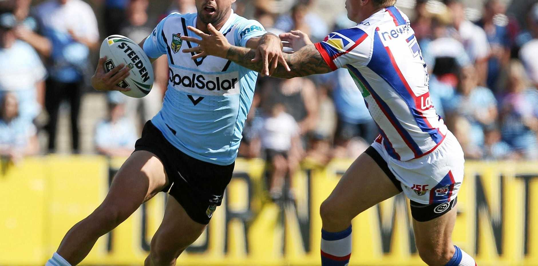 Gerard Beale of the Sharks is tackled by Trent Hodkinson of the Knights.