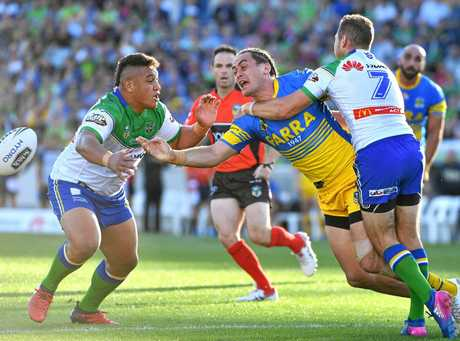 Brad Takairangi of the Eels gets a pass away against the Raiders.