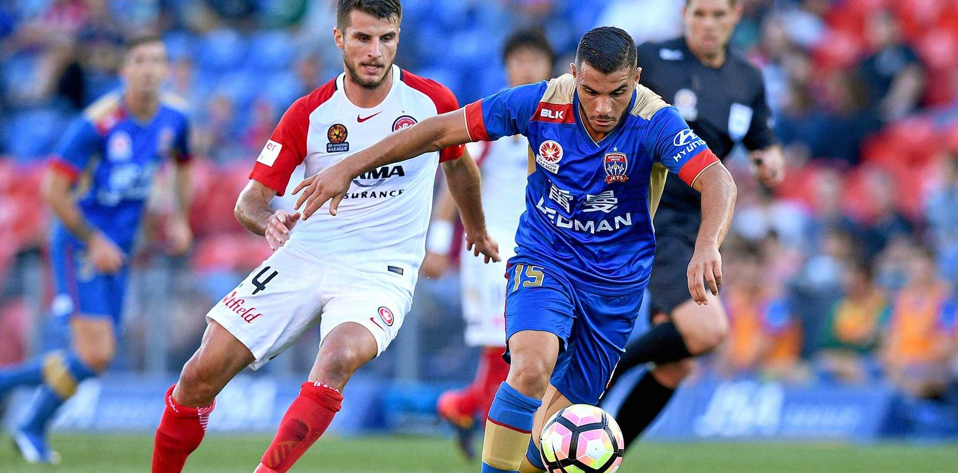 Andrew Nabbout of the Jets competes for possession with Terry Antonis of the Wanderers.