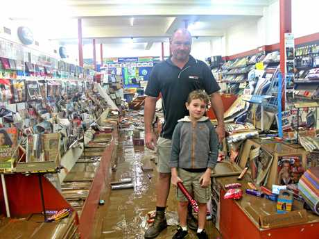 DELUGE: Keiran Scott and his son Sebastian have a long road ahead to clean up their newsagency in Molesworth St, Lismore.