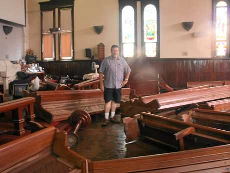 DISASTER: Robert Griffith, the senior minister of the Lismore Uniting Church, closes his eyes as stands amidst the ruin and wreckage of the flood in the church and contemplates the work ahead.