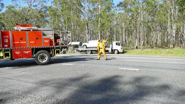 Emergency service workers clean up a crash site on the Pacific Highway at the intersection of Four Mile Lane, where two cars collided head-on on Sunday morning.