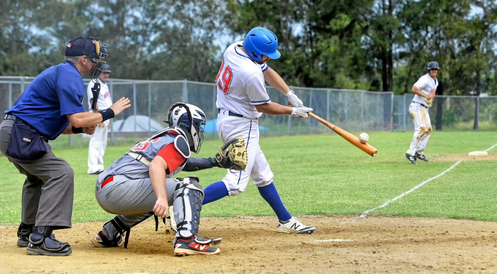 A Musketeers batter feels bat on balls during their match with the Redcliffe Padres on Sunday.