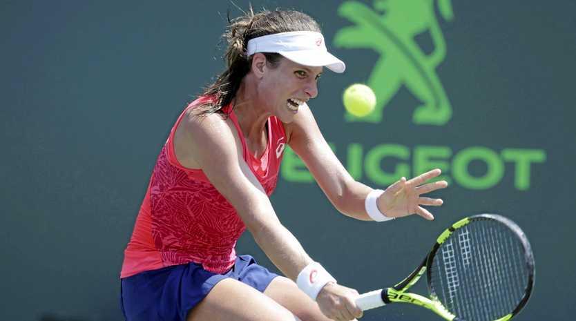Johanna Konta, of Britain, hits a return to Caroline Wozniacki on her way to winning the Miami Open.