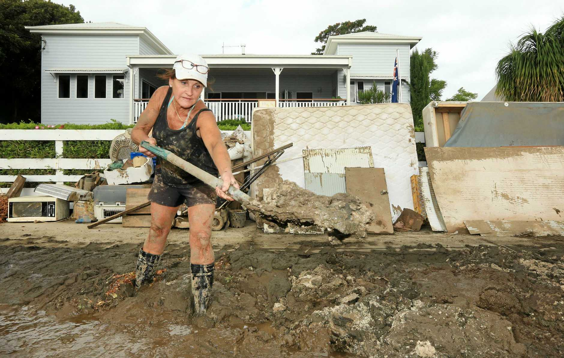 Julie Castles from Tumbulgum shovels thick river mud from her footpath after heavy flooding on Thursday night caused the Tweed River to break its banks.Photo: Scott Powick Daily News