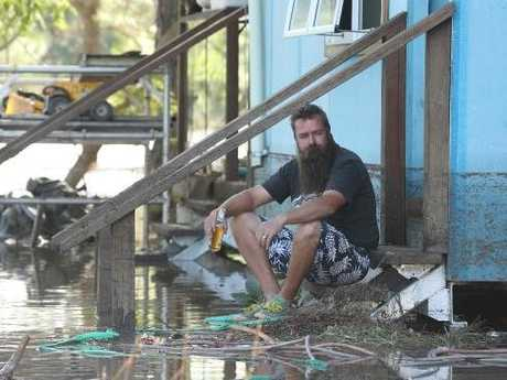 Trent Green sits on the steps having beer waiting for the flood waters to subside around his flood destroyed home in Loganlea.