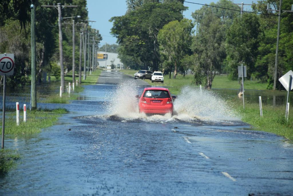 A motorist risks driving through flood water on Port Curtis Rd.
