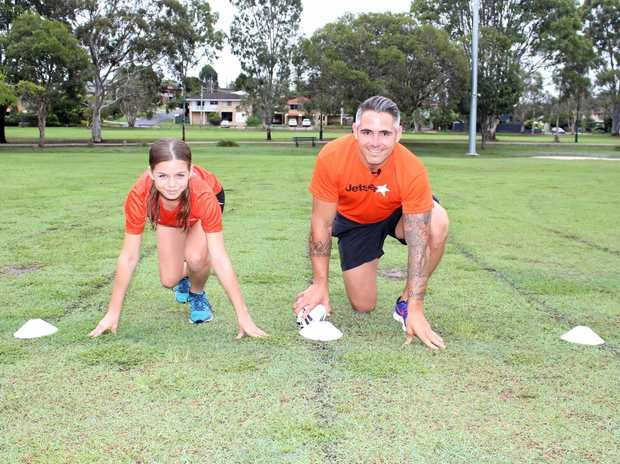 Brooke Currie receives some training tips from rugby league legend and Little Athletics alumni Corey Parker at Bracken Ridge Little Athletics.