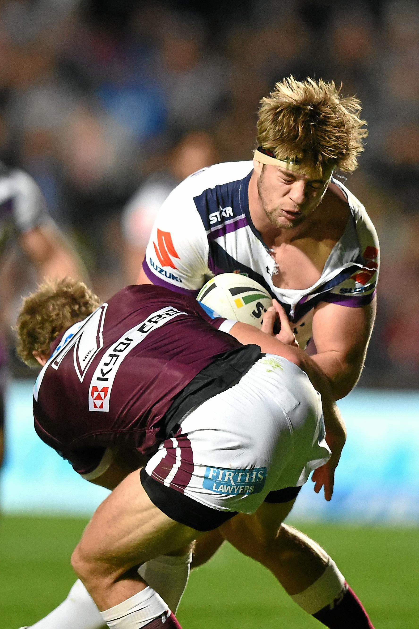 Christian Welch of the Storm is tackled by Daly Cherry-Evans of the Sea Eagles.