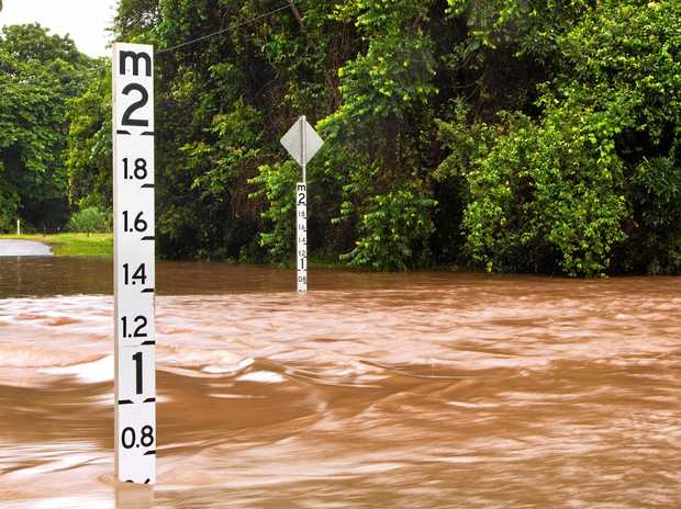 A flooded road with depth indicators in Queensland, Australia