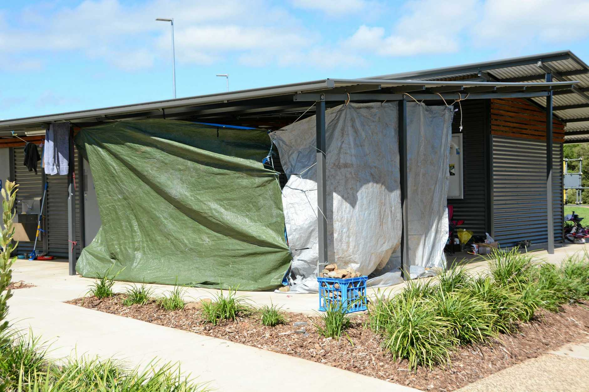 THIN VEIL: Tarpaulines act as a buffer to the bitter winds at Clewley Park off Water St where about 16 people sleep every night.