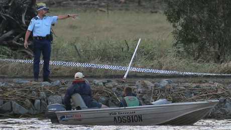 Matt Grinham and son Thomas Grinham, 15, use a depth sounder to locate the car in the river.