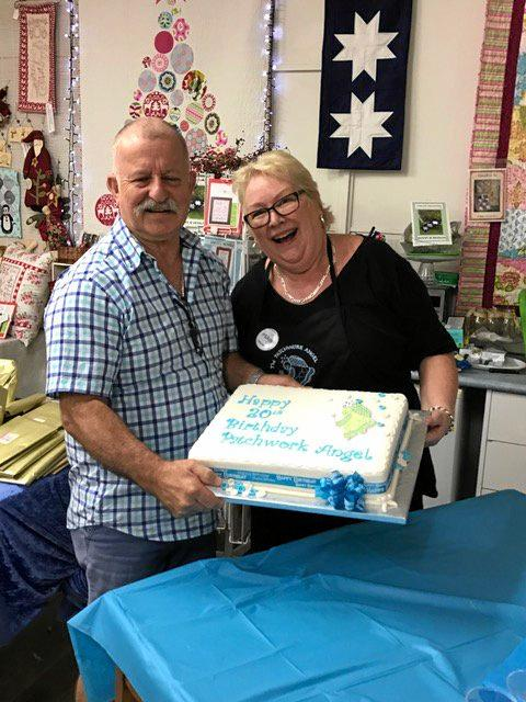 Penny and Chuck Hornbuckle from The Patchwork Angel, celebrate 20 years by cutting cake for their guests.
