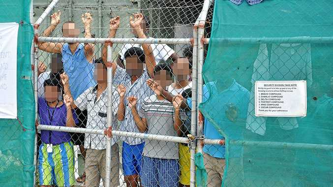In this 2014 image, asylum seekers stare at media from behind a fence at the Manus Island detention centre, Papua New Guinea.