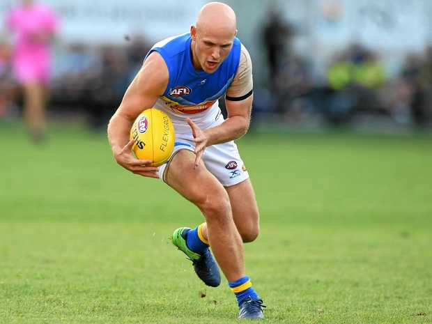 Gary Ablett of the Suns picks up a loose ball against the Giants.