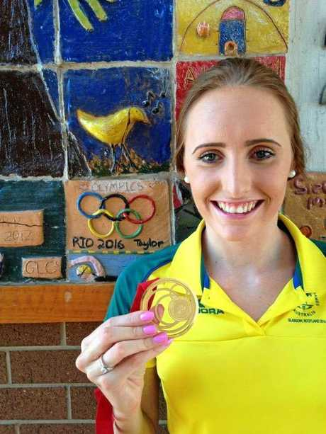 WINNERS GRIN: Taylor McKeown next to her year 12 graduation tile after she won Commonwealth gold.
