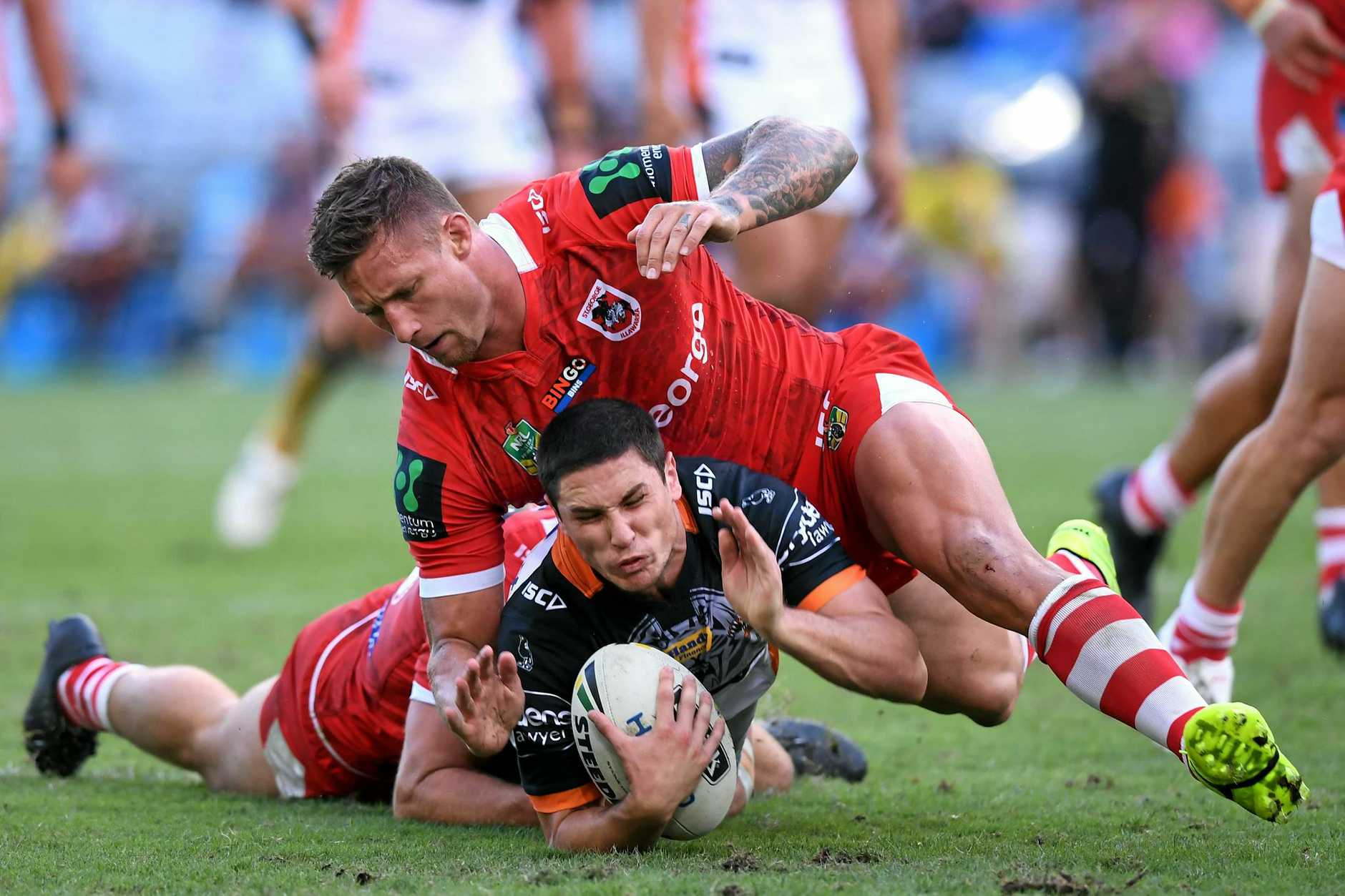 Mitchell Moses (centre) of the Tigers is tackled by Tariq Sims (right) of the Dragons.