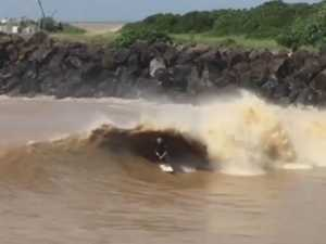 Surfers ride flood wave.