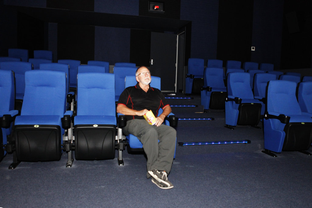 Hervey Boat Club CEO Ed Gibson tests out the seats of the venue's new cinema, Marloo, as well as some popcorn.