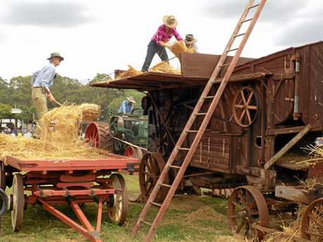 BROUGHT TO LIFE: Volunteers work the grain thresher at last year's festival.