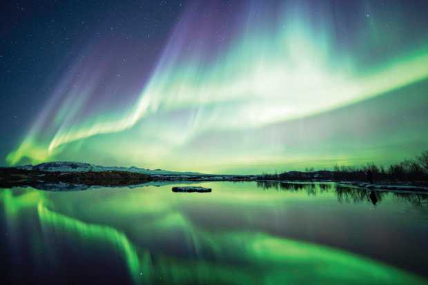 Tromso is one of many places to watch the Northern Lights blaze, as is Lake Thingvellir National Park in Iceland.