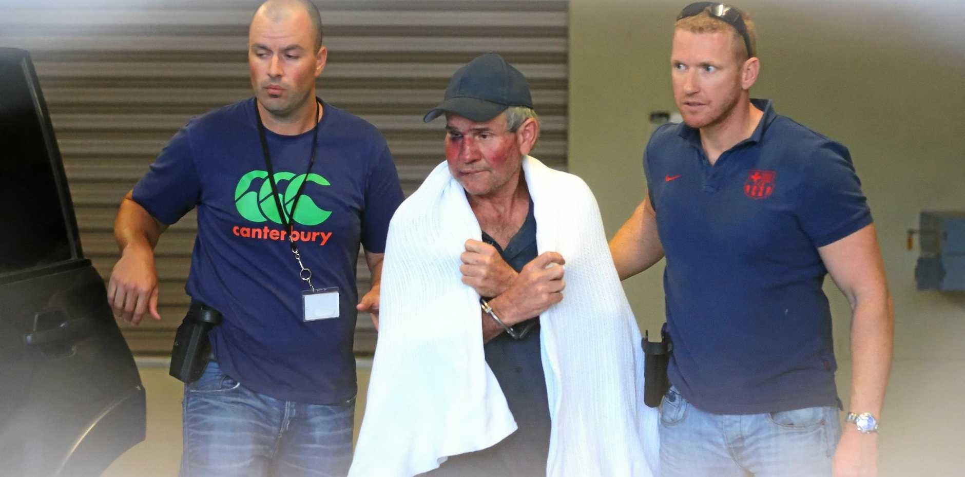 Gino Stocco is escorted by two policemen as he is taken into Dubbo police station after he and his son Mark were arrested earlier in the day in Dunedoo in north west NSW. Wednesday, Oct. 28, 2015.