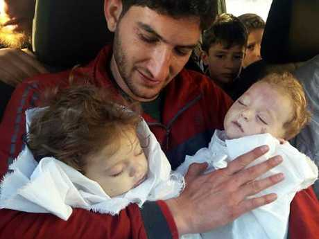 Abdul-Hamid Alyousef, 29, holds his twin babies who were killed during a suspected chemical weapons attack.
