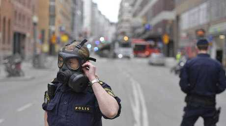 A police officer in a gas mask attends the scene after a truck crashed into a department store injuring several people in central Stockholm, Sweden, Friday April 7, 2017.