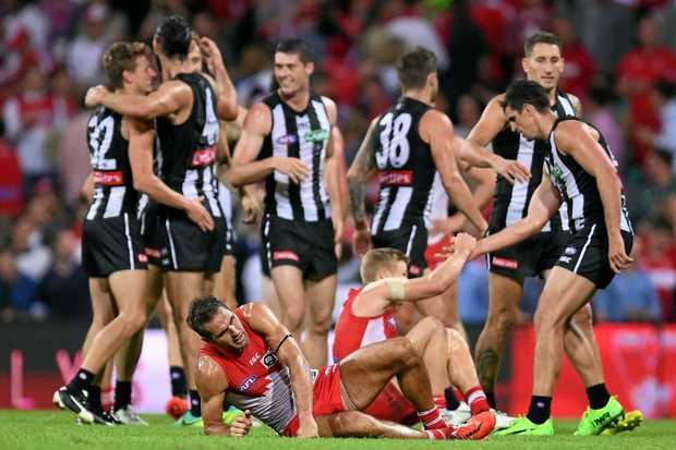 The Swans' Josh Kennedy lays on the ground as the Magpies celebrate their win over Sydney.
