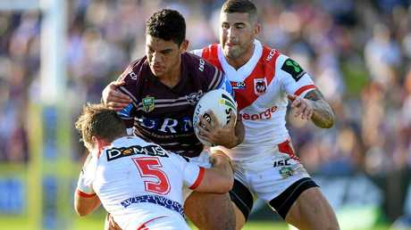 Brian Kelly of the Sea Eagles is tackled by Kurt Mann (left) and Joel Thompson of the Dragons.