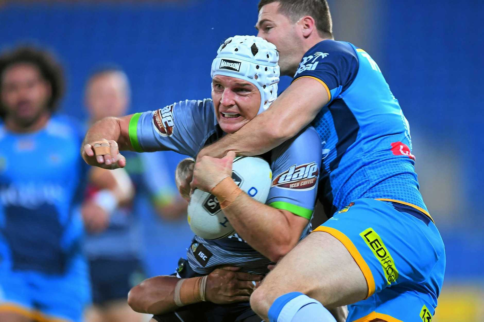 Jarrod Croker of the Raiders is tackled by the Titans.
