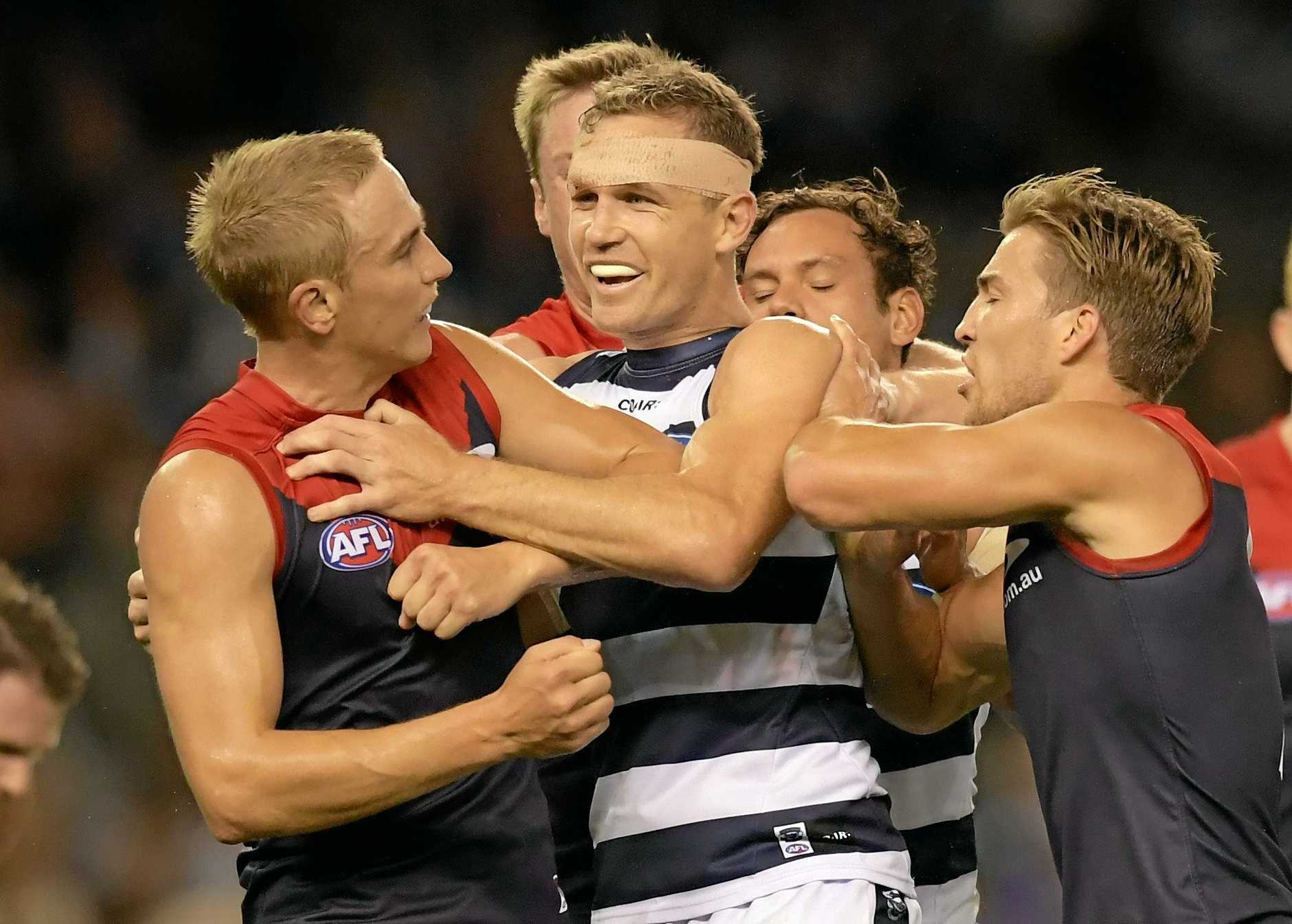 A fight breaks out between Joel Selwood of the Cats (right) and Bernie Vince of the Demons.