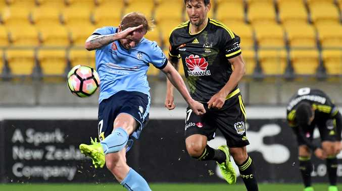 David Carney of Sydney FC attempts a long-range shot in front of Vince Lia of the Phoenix.