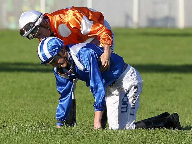 Jockey Blake Shinn helps James Doyle after they were dislodged in the Sydney Cup,