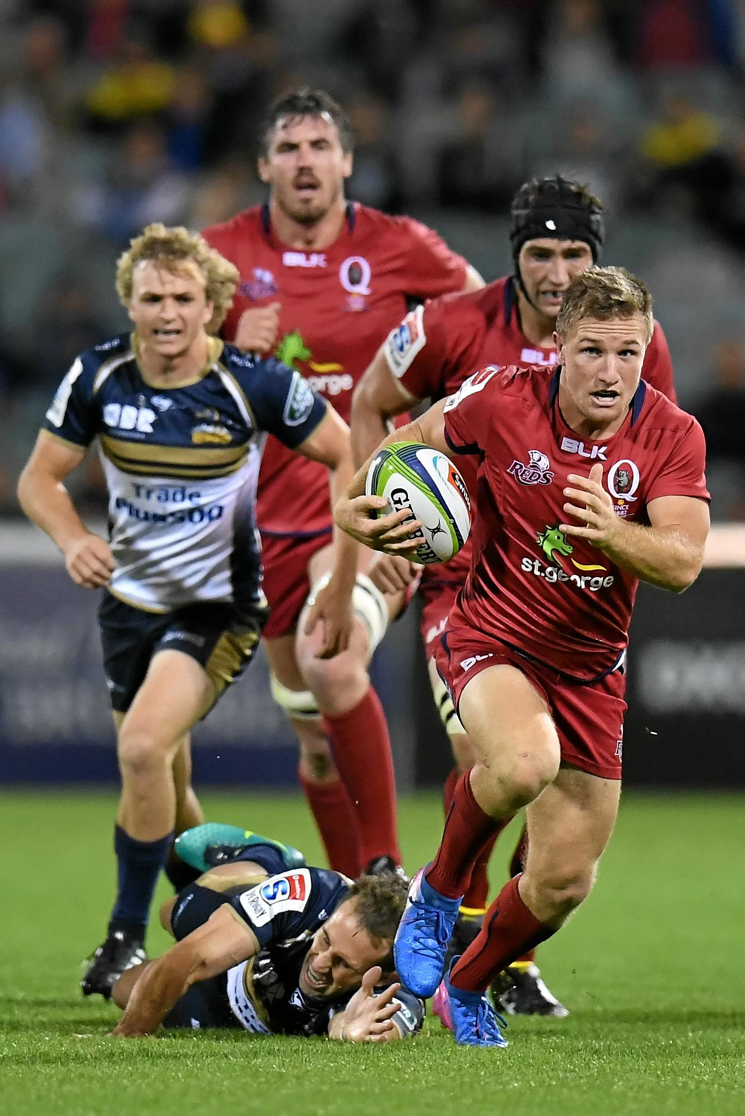 James Tuttle of the Reds evades a tackle by Andrew Smith of the Brumbies.