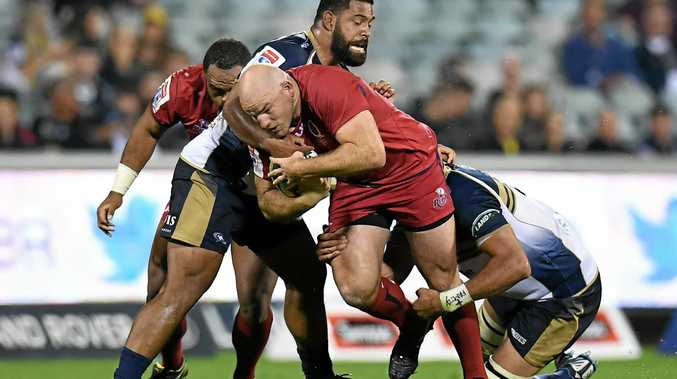 Scott Sio and Rory Arnold of the Brumbies tackle Stephen Moore of the Reds.