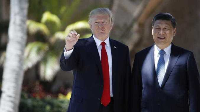 President Donald Trump and Chinese President Xi Jinping pause as they walk together at Mar-a-Lago, Friday, April 7, 2017, in Palm Beach, Fla.