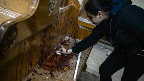 A woman wipes the blood of victims off a church bench at the scene of a bomb explosion inside Mar Girgis church in Tanta, 90km north of Cairo, Egypt,