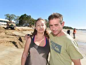 Couple sink in sand on Torquay Beach