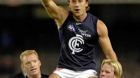 Carlton's Anthony Koutoufides is carried off the ground by teammates Lance Whitnall and Nick Stevens after playing his 250th AFL match in 2006.