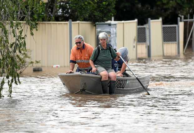 Wayne and Glenda Wisley steers their boat through the flooded streets of Depot Hill in Rockhampton, Thursday, April 6, 2017. Floodwaters resulting from ex-cyclone Debbie are expected inundate parts of Rockhampton with the Fitzroy River expected to reach 9 metres at midday on Thursday. (AAP Image/Dan Peled) NO ARCHIVING