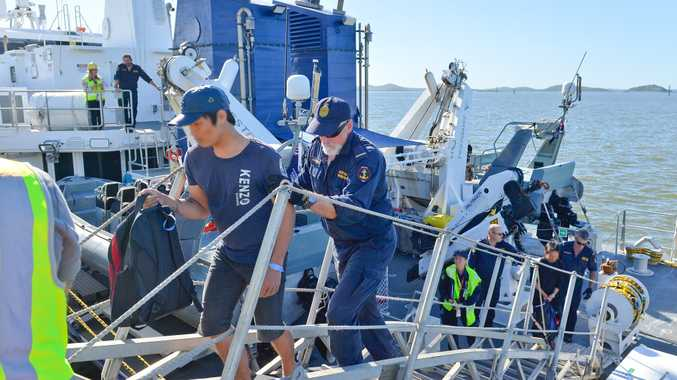 Border force officers escort illegal fisherman to shore in Gladstone from the ship Cape Jervis after they were intercepted yesterday.