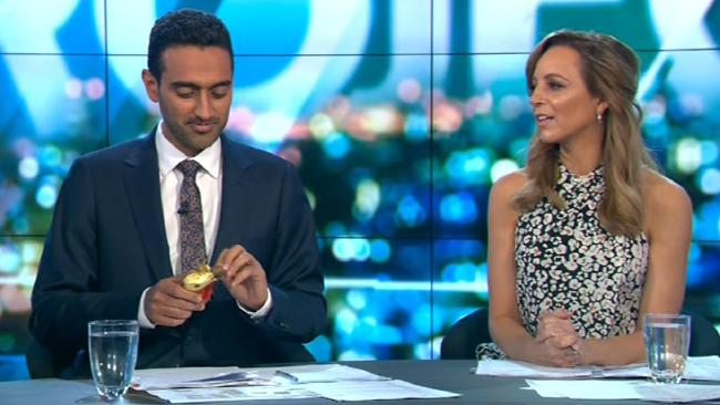 Waleed Aly takes a big bite out of the Lindt chocolate Easter egg.