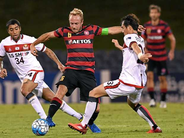 Mitch Nichols (centre) of the Wanderers is tackled by Lee Seok-hyun of Seoul.