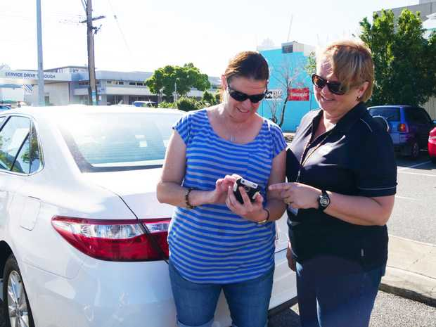 Local Laws officer Tracey Browne (right) shows Kristie Brown how to use the new PayStay app.
